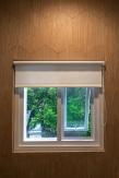 Jendela yang tampil pada fasad rumah, dilihat dari dalam.